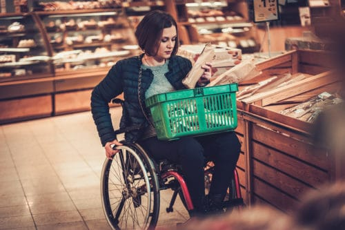 Rollstuhlfahrerin beim Einkauf